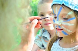 Outdoor play activities like face painting with neon colours helps to stand out whilst playing hide and seek