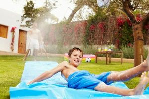 Father and kids having fun on a water slide in their garden using the hose